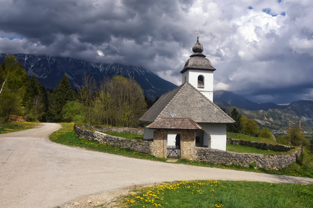 St. Katarina church (Sveta Katarina na Homu) on a spring meadow hill above Zasip village near Bled in front of the Stol mountain covered by dark clouds, Slovenia