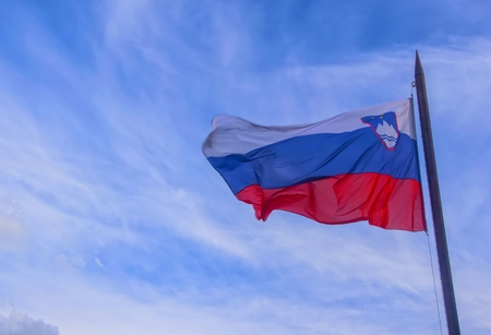 Slovenian national official flag on flagpole waving in the wind on picturesque blue sky background Stock fotó