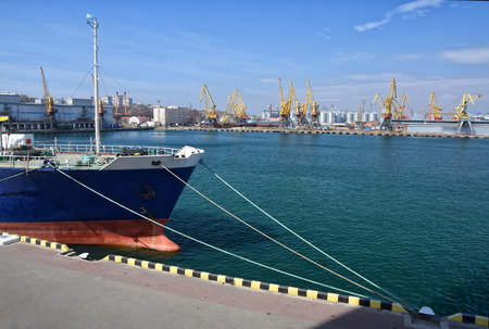 ship bow: Bow of moored vessel on the pier with seaport cranes and tanks background