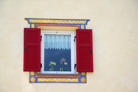 orchid house: Beautiful window with red shutters and orchid pots behind glass in a small alpine country house