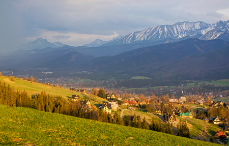 Scenic view of Koscielisko village near Zakopane with panorama of snow caped High Tatras on background, Poland in sunlit at spring evening Stock Photo