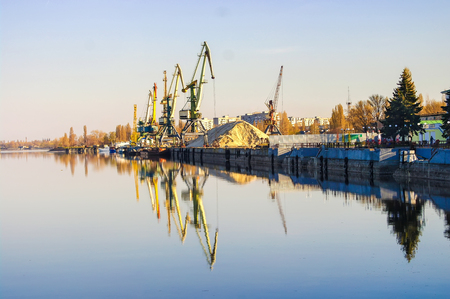 clearly: Row of cargo port cranes reflected in calm river water