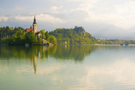 Island on Bled lake and pilgrimage church of the Assumption of Mary with spring mountain landscape background reflected in water at sunny day, Slovenia