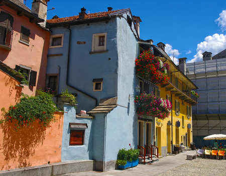 Old colorful medieval buildings with flowered balcony in Domodossola, Piedmont, Italy