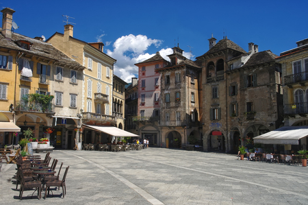 View on central square - Piazza del Mercato - of Domodossola with medieval buildings and street cafes under blue sky, Piedmont, Italy