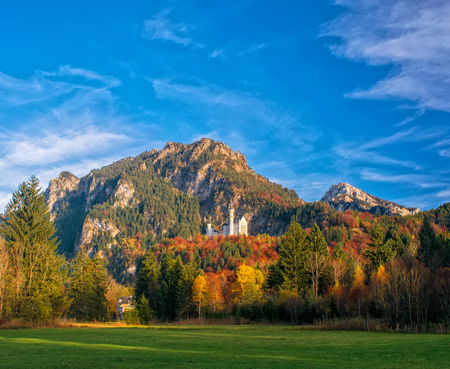 Amazing view on Neuschwanstein Castle with picturesque sky and colorful trees at autumn sunny day, Bavaria, Germany