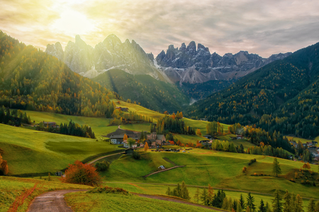 Colorful autumn scenery in Santa Maddalena village with church, roads and meadows on foreground and mountain peaks on background at sunrise. Dolomite Alps, South Tyrol, Italy.