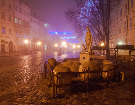 Christmas decoration as part of nativity scene with hay sheep on Market square at foggy evening, Lviv, Ukraine Stock Photo