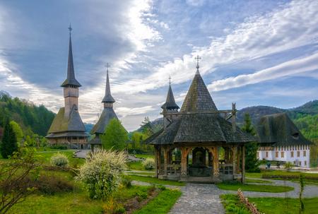 Arquitectura de madera tradicional de Maramures del monasterio de Barsana en el día de primavera clody, Rumania Foto de archivo - 90669892