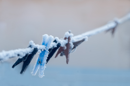 Frozen colorful clothes-pins on a rope at winter morning 版權商用圖片 - 91729956