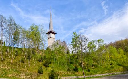 Traditional Maramures wooden noe-gothic church in Barsana monastery at clody spring day, Romania