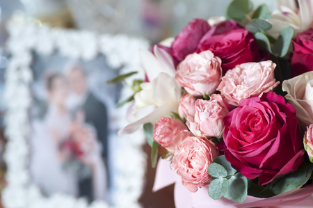 Bridal bouquet of red, pink and white roses near photo of newlyweds in frame
