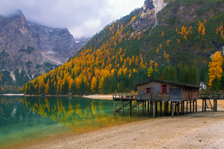 Beautiful autumn alpine landscape, spectacular old wooden dock house with pier on Lago di Braies Lake (Pragser Wildsee), Dolomites, Italy