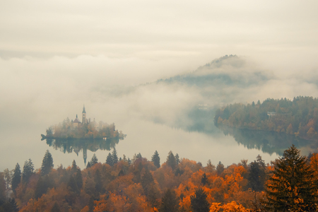 Amazing view of Lake Bled at foggy autumn morning with colorful forest on foreground and mountains covered by clouds on background, Slovenia