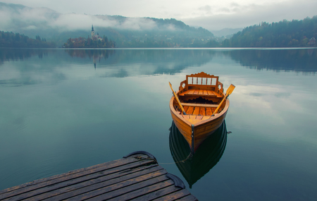 Lonely boat on the water surface of Bled lake at foggy autumn day, Slovenia