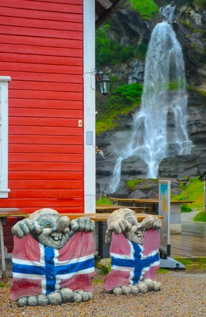 Two sculptures of trolls - mythological symbol of Norway - with norwegian flags and Steinsdalsfossen waterfall in the background, Norway Stock Photo