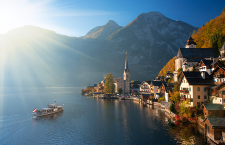 Scenic view of famous Hallstatt mountain village in the Alps with traditional passenger ship at autumn morning.  Upper Austria
