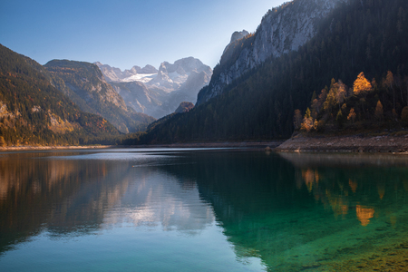 Autumn scenery of Gosausee lake with mountains reflected in the surface water and Dachstein mountain summit  on background, Salzkammergut region, Upper Austria