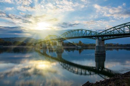 Amazing view of Maria Valeria bridge with reflection in Danube river on Slovak-Hungary border at sunrise. Esztergom, Hungary. Autumn morning. Travel destination