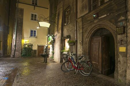 Bicycles parked on empty medieval street in old city of Innsbruck at night, Tirol, Austria