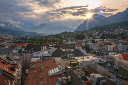 Aerial view of old city center, colorful buildings on Inn river bank and Alps mountains in background taken from town hall tower at sunset, Tirol, Austria