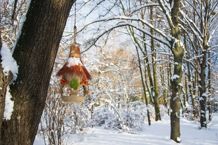 Decorative colorful feeder covered snow in winter forest.