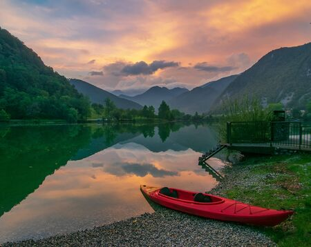 Picturesque sky over reservoir on Soca river near Most na Soci, Slovenia at sunset. Red kayak on foreground. Soca river - popular place for active recreation in Julian Alps Фото со стока