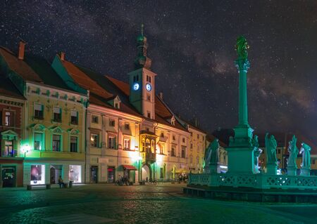 Scenic nightscape of Main Square of Maribor under starry sky. Plague Column and Town Hall building. Maribor is the second largest city of Slovenia and popular travel destination Reklamní fotografie