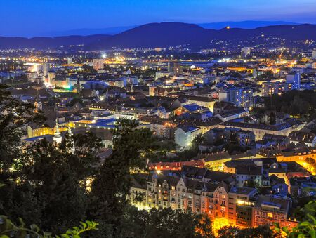 Panoramic view of the city of Graz, Austria at night. Illuminated streets and mountain hills on background. Aerial view from castle hill.