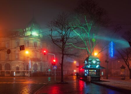 Beautiful nightscape of city center of Lviv, Ukraine at foggy night with wet pavement and newsstand on foreground.