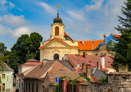 Scenic view of Kutna Hora with old house rooftops and Ursuline Convent Church in city center, Czech Republic at sunny summer day.