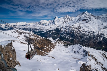 Cable car against breathtaking panoramic view of snow capped Swiss Alps with famous peaks Eiger, Monch and Jungfrau, Berner Oberland, Switzerland Reklamní fotografie