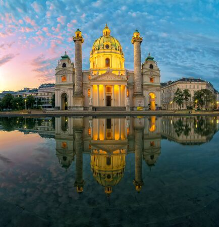 Amazing view of Karlskirche or St. Charless Church - one of famous churches in Vienna - under picturesque morning sky with illumination and reflection in the water at sunrise, Vienna, Austria.