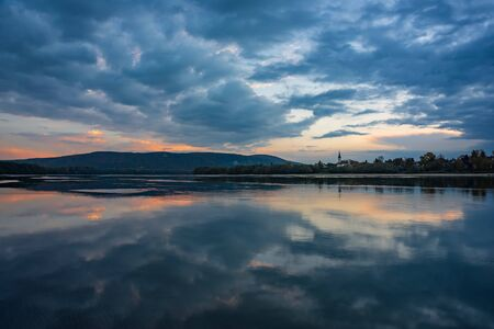 Amazing sunrise view over Danube river, beautiful reflections of morning clouds mirrored in water, Esztergom, Hungary. Travel destination scene