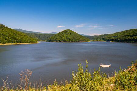 Artificial lake Zetea on Tarnava Mare river, Eastern Carpathians, Romania at sunny summer day