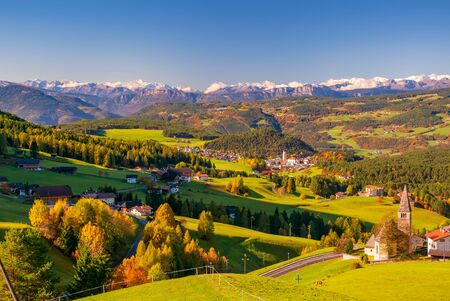 Incredible scenic view of traditional tyrol village with churches in alpine valley at autumn sunny day. Snowcaped mountain range on background. San Michele and Castelrotto, South Tyrol, Italy