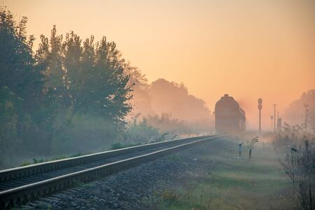 Morning diesel train passing in the autumn haze at sunrise light