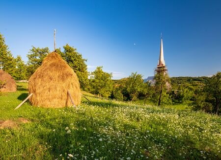 Scenic rural landscape with traditional maramures wooden church on background and haycock and green meadow on foreground in Maramures