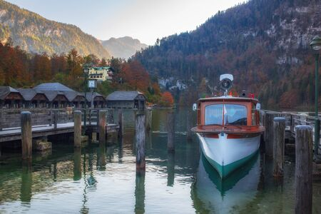 Wooden pier with touristic ship on picturesque Lake Konigssee at autumn, Bertechsgarden Alps, Bavaria, Germany. Great mountains of Canyon on background