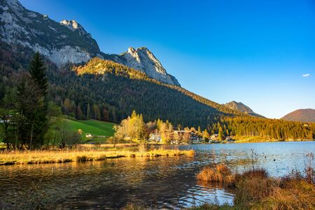 Picturesque autumn evening over Hintersee lake. Sunlit slope of Berchtesgaden Alp mountains on the Austrian border, Bavaria, Germany. Stock Photo