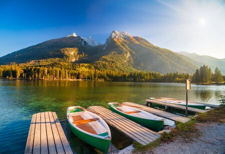 Amazing autumn scenery on Hintersee lake with boats moored on wooden pier. Picturesque evening. Berchtesgaden Alps, Bavaria, Germany