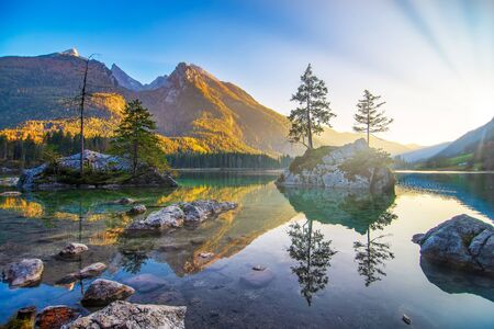 Majestic autumn sunset on Hintersee lake. Beautiful scene of trees on a rock islands, sunlit mountains reflected in the water. Berchtesgaden Alps, Bavaria, Germany