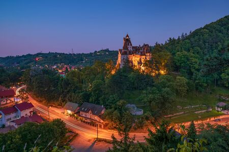 Picturesque nightscape of famous Bran castle. It is known for the myth of Count Dracula and the most visited tourist attraction in Romania. Light trail left by cars. Transylvania, Romania