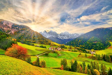 Picturesque autumn scenery in Santa Maddalena village with church, road, colorful trees and meadows on foreground and mountain peaks on background at sunrise. Dolomite Alps, South Tyrol, Italy