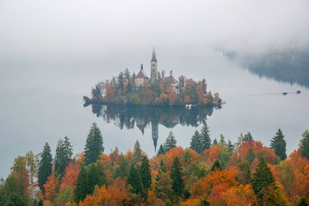 Amazing view of Lake Bled at foggy autumn morning with colorful forest on foreground and Bled island with pilgrimage church of the Assumption of Mary on backgroung, Slovenia