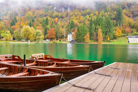 Picturesque autumn scenery with boats moored on the quay of Lake Bled with colorful trees on opposite lakeshore, Slovenia