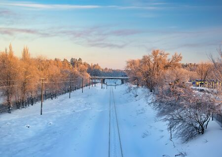 Scenic view of railway going along snowy trees illuminated by rising sun