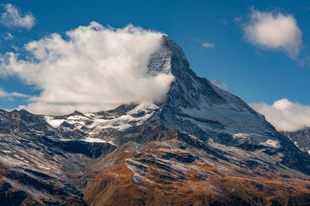 Stunning autumn scenery of famous alp peak Matterhorn covered by fluffy cloud. Swiss Alps, Valais, Switzerland