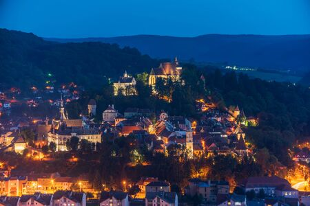 Picturesque top panoramic view of old town of Sighisoara, Transylvania, Romania at night. Illuminated towers and churches in old city. Birthplace of Vlad Dracula.