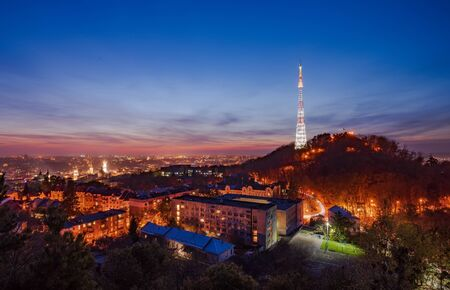 Amazing panoramic view of High Castle hill with TV tower and old quarters in historical city center illuminated at twilight against picturesque sunset sky, Lviv, Ukraine. UNESCO world heritage site